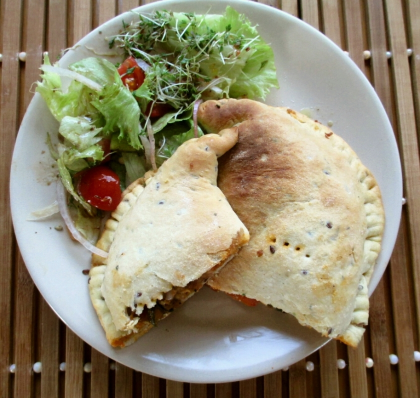 vegan calzone stuffed with olive, basil, tomatoes, red onion and almond parmasan